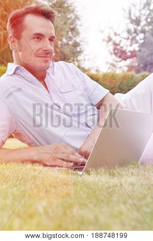 Young man using laptop while looking away in park