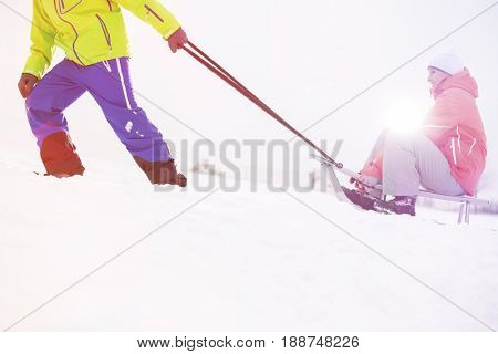 Low section of man giving sled ride to woman in snow