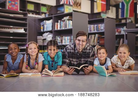 Portrait of teacher and schoolkids lying on floor while reading books in library at school