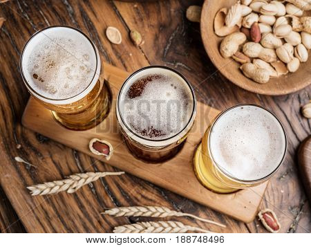 Glasses of beer and snacks on the wooden table. Top view.