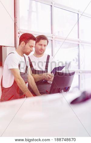 Male repair workers working in automobile repair shop