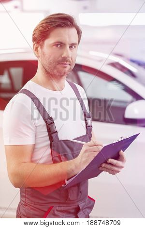 Portrait of confident automobile mechanic writing on clipboard in workshop