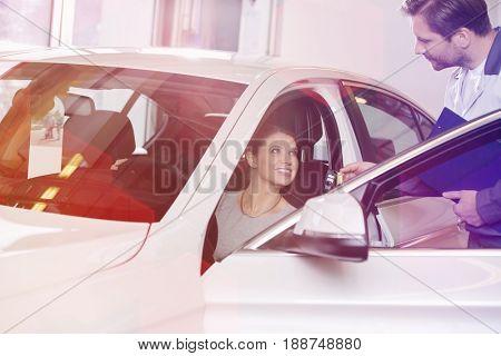 Female customer receiving car key from mechanic in automobile repair shop