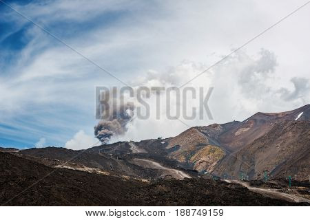 Scenic view of Mount Etna erupting with cloud of ash in sky on island of Sicily
