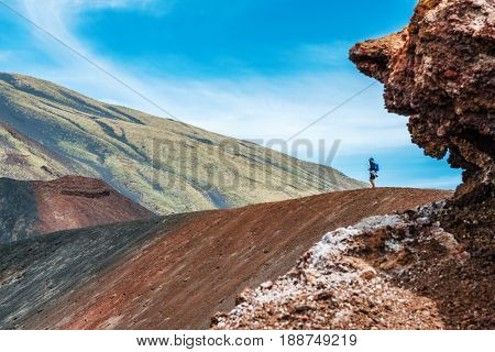Tourist stood on Mount Etna volcano looking at crater, Sicily