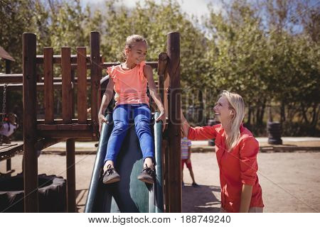 Trainer interacting with girl while playing on slide at school playground