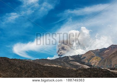 Spume of smoke and ash billowing from a vent on Mount Etna volcano Sicily, Italy against a blue sky