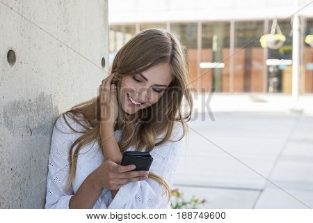 Young female university student on college campus using her smartphone and smiling standing outside near wall with copy space