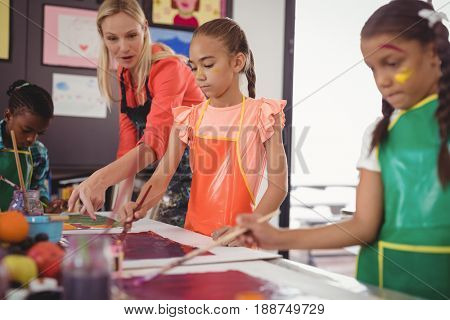 Teacher assisting schoolkids in drawing class at school