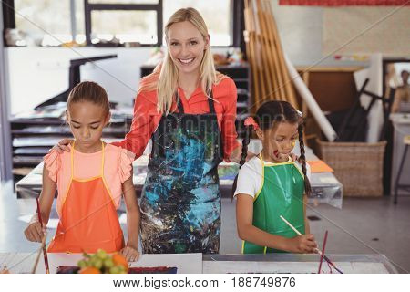 smiling teacher standing with schoolkids in drawing class at school