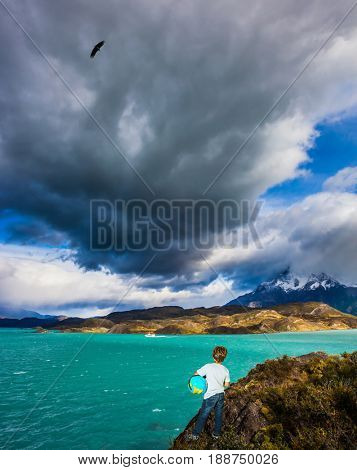 Boy with a globe under his arm on the shore of lake Pehoe. Chile, Patagonia, Torres del Paine National Park - Biosphere Reserve