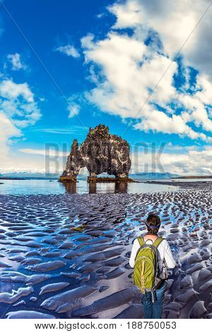 The Basalt rock - Mammoth Hvitsercur during an ocean outflow. Concept of extreme northern tourism in Iceland. Woman with a green backpack admiring the natural wonder
