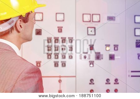 Rear view of young male supervisor examining control room in industry