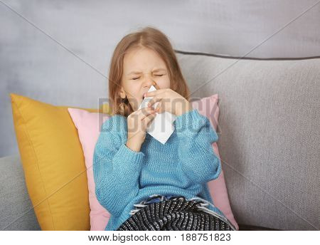 Small ill girl with napkin at home