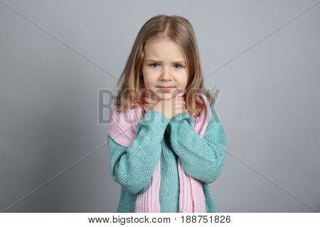 Little ill girl with sore throat on color background. Concept of allergy