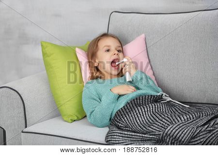 Small ill girl with spray on couch at home