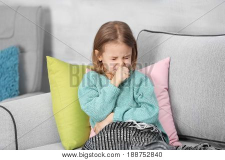 Small ill girl on couch at home