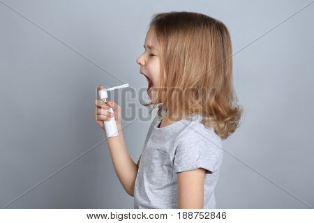 Small ill girl with spray on grey background