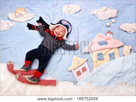 Happy smiling infant baby boy skier, skiing in snow mountains, wearing scarf and warm hat. Textile decoration of a winter city.