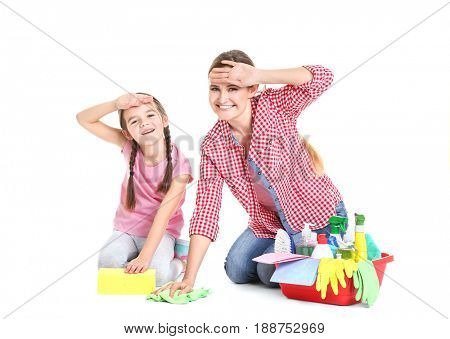 Mother and daughter with cleaning supplies, isolated on white