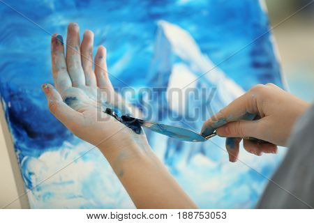 Female artist working with palette knife, closeup