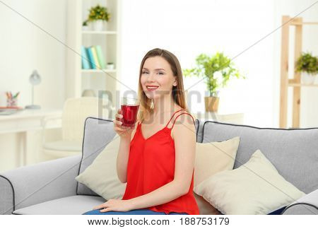 Beautiful woman drinking fresh juice at home