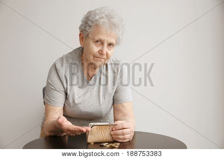 Senior woman counting coins while sitting at table. Poverty concept