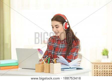 Beautiful young woman sitting at table and listening to audiobook