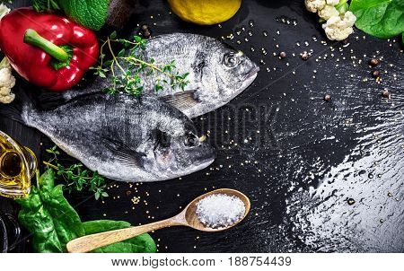 Fresh fish dorado top view. Spicy herb and vegetables healthy food spice on black stone board cooking. Copyspace.