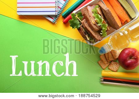 Concept of school lunch. Lunchbox, food and stationery on color background