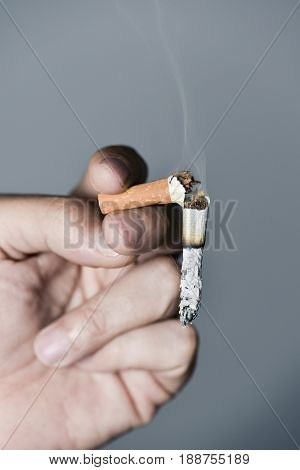 closeup of a young caucasian man with a broken lit cigarette in his hand