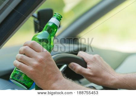 Man holding green bottle of beer in hand while driving a car. Don't drink and drive concept