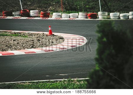 corner of the gokart track with curb and cone on new asphalt surface with tree in foreground