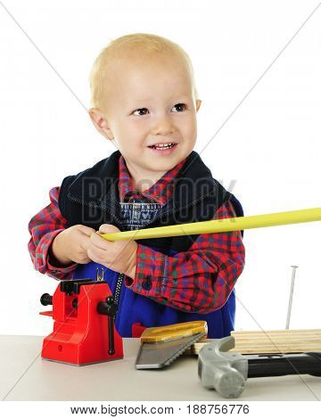 Ad adorable toddler playing tool man.  He's holding one end of a tape measurer, while the other is being held out of the viewer's sight.  On a white background.