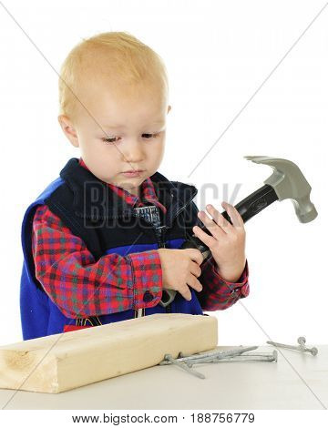 An adorable toddler sadly looking at a block of wood and nails with a toy hammer in his hands.  On a white background.