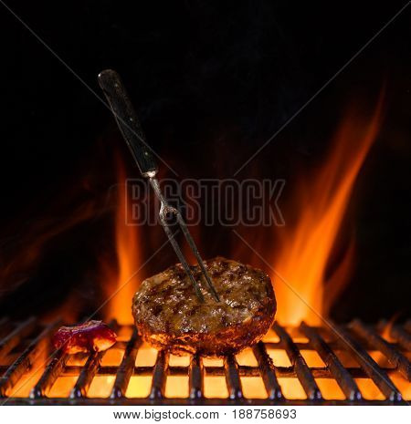 Beef milled meat for hamburger placed on the grill grate, flames on background. Barbecue and grill, delicious food.