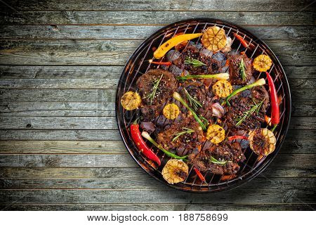 Top view of fresh beef steaks and vegetable on grill placed on wooden floor. Barbecue, grill and food concept