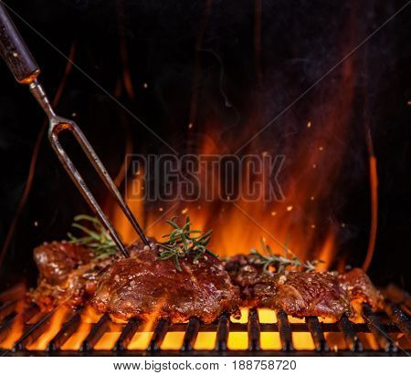Beef raw steaks on the grill grate with fork, flames on background. Barbecue and grill, delicious food.