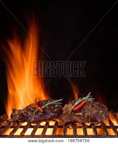 Beef steaks on the grill grate, flames on background. Barbecue and grill, delicious food.