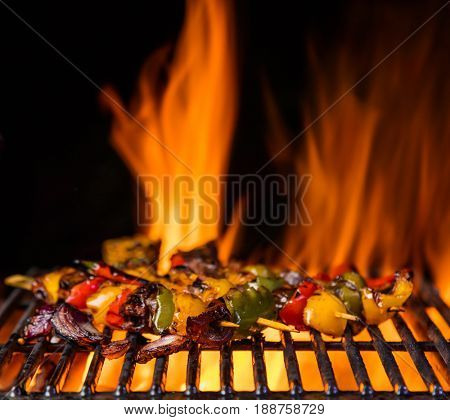 Meat and vegetable skewer on the grill grate, flames on background. Barbecue and grill, delicious food.