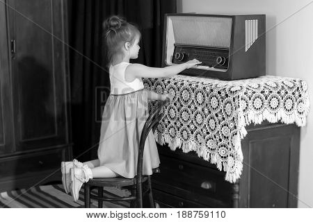 Curious little girl looking at a vintage radio . She is trying to push on the keys.Black-and-white photo. Retro style.