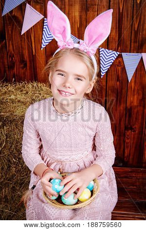Easter holidays. Cute little girl in Easter Bunny costume holding colorful Easter eggs and smiling.
