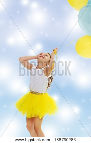 Pretty little blonde girl in a short bright yellow skirt and white blouse.Girl holds in hands balloons , She looks at them from the bottom up.Blue Christmas festive background with white snowflakes.