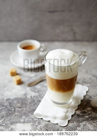 Glass of Latte Macchiato and a cup of espresso on stone background