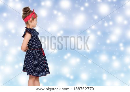 Cute little girl in a short blue dress with polka dots. With a red bandage on his head.Girl turned sideways to the camera. Close-up.Blue Christmas festive background with white snowflakes.