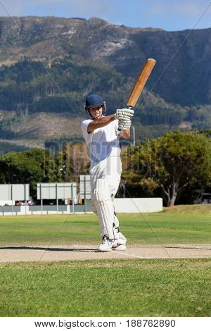 Full length of batsman playing cricket on field during sunny day