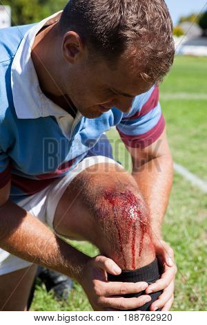 Injured rugby player kneeling on playing field during sunny day