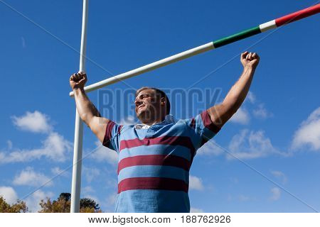 Low angle view of smiling rugby player with arms raised by goal post against blue sky