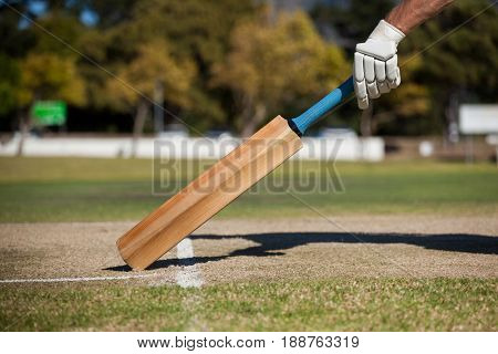 Cropped image of player scoring run on cricket field