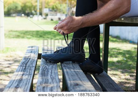 Low section of rugby player tying shoes while sitting on bench during sunny day